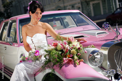 Bride sat on pink cadillac limousine smiling