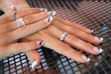 Beauty women hands with rings and varnished fingernails poster