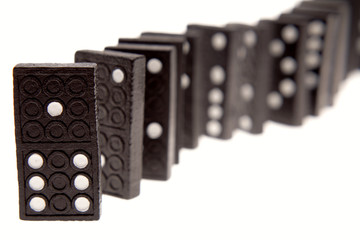 Dominoes standing in a row over white
