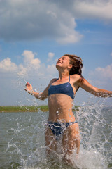 girl jumping in water with splashes