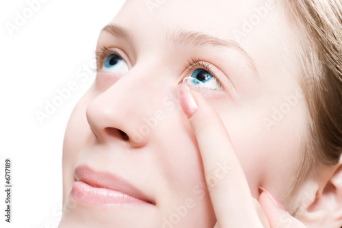 Young woman puting a contact lens