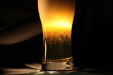 High glass of beer with blebs and foam on dark background poster