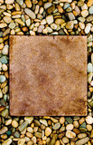 Square stone slab surrounded by grungy pebbles poster