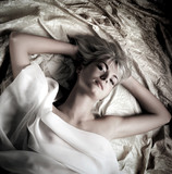 Monochrome portrait of a lovely beautiful girl lying in a bed poster