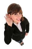 Businesswoman with hand to ear listening