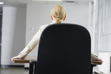 Rear view of a business woman sitting on a chair in an office.