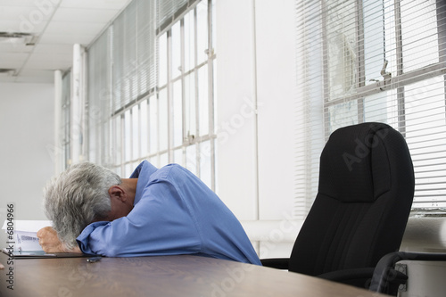 View of a tired business man resting his head on a table.