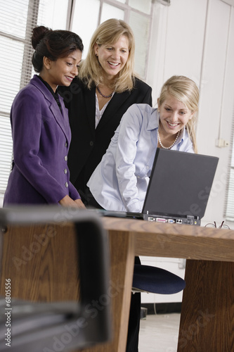 Three business colleagues looking at a laptop.