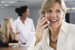 A smiling business woman using a cellphone.