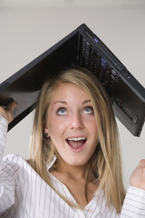A woman with a laptop over her head.