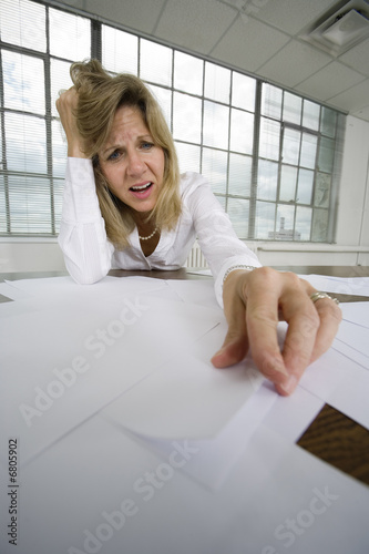 A depressed business woman looking at papers.
