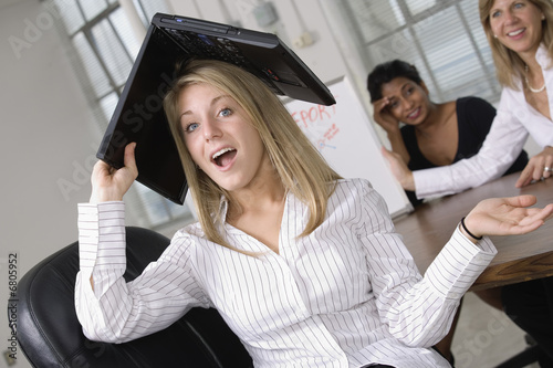 Portrait of a business woman with a laptop over her head.