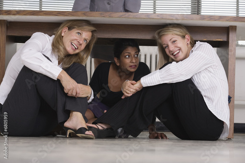 Three business woman hiding under a desk.