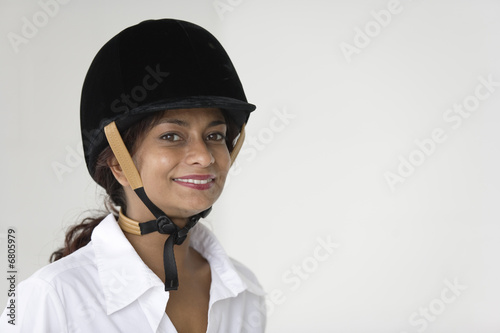 Portrait of cheerful woman wearing an equestrian hard hat.