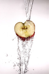 Apple with water pouring over it on white