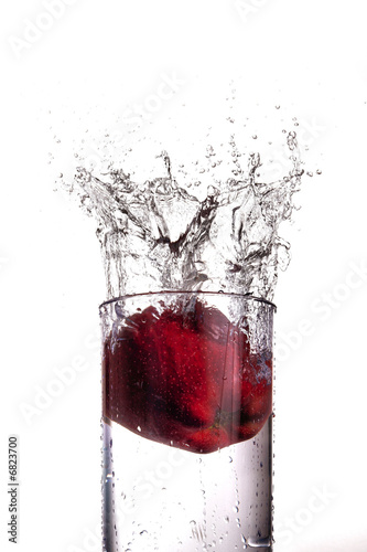 Apple splashing into a glass of water
