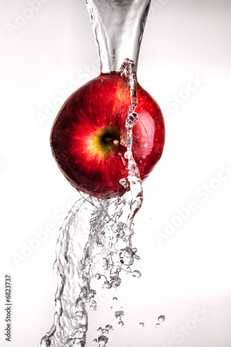 water pouring over apple on white