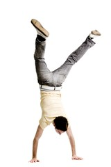 Young adult male doing a handstand on a white background