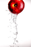 Water pouring  and splashing over a red delicious apple on white