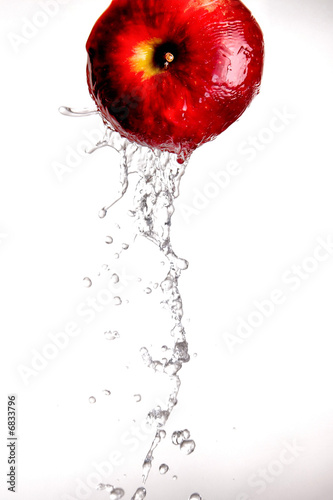 Leinwanddruck Bild Water pouring  and splashing over a red delicious apple on white