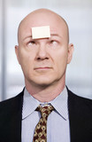 Businessman with a blank note on his forehead poster