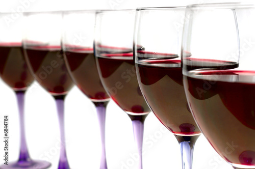 glasses of red wine in a line, on white