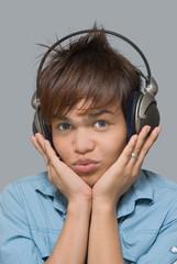 Teen with headphones holding his head