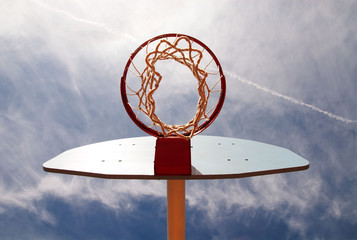 Basketball hoop shot from underneath in a cloudy blue sky.