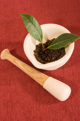 Mortar and Pestle with Peppercorns and Bay Leaf
