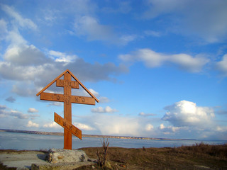 Wooden christian crossc on the coast of the river.