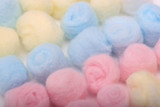 Blue, yellow and pink hygienic cotton balls in rows poster