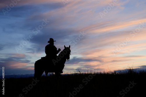 Cowboy on horseback back lit by the dawn sky
