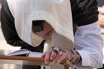 Praying Jew on Jerusalem Western wall during sabbath