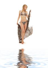 walking bikini girl with sarong  on white sand