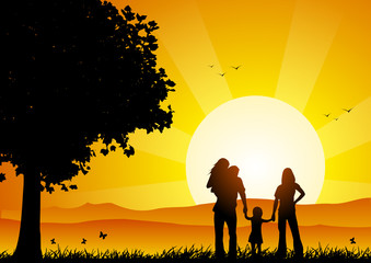 Happy family at sunset under a tree