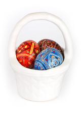 three easter eggs in white basket over white