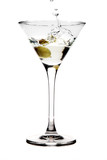 Splashing olive into a martini glass