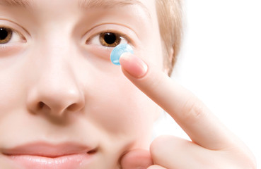 Young woman puting blue contact lens