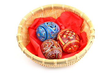 three russian tradition easter eggs in yellow basket
