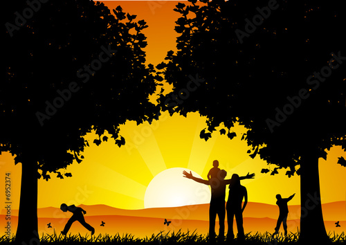Happy family at sunset under the tree
