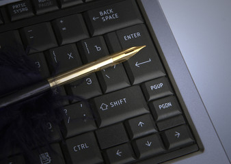 Feather quill on laptop