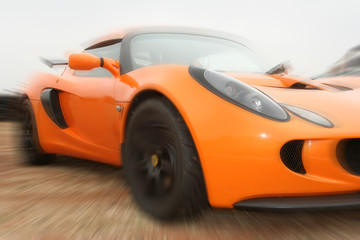 Artistic blur of orange motor car.