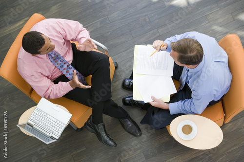 Overhead View Of Two Businessmen Having Meeting In Office Lobby