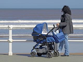 Madre con cochecito de bebe en la playa