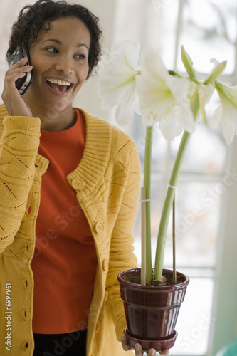 Black woman on cell phone admiring a flower