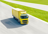 vivid yellow truck in motion under bright sun on highway poster