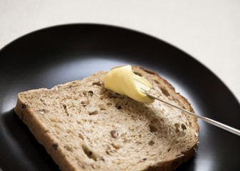 Slice of Granary Bread being Spread with Butter