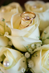 Wedding rings (close-up on wedding bouquet from yellow roses)