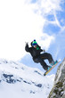 Male snowboarder jumping with snowboard