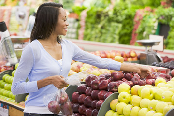 Woman shopping for apples at grocery store